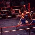 As one boxer advances the opponent is back into the corner.