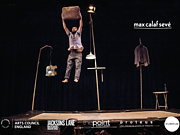 An performer in mid jump, with a suitcase held aloft.